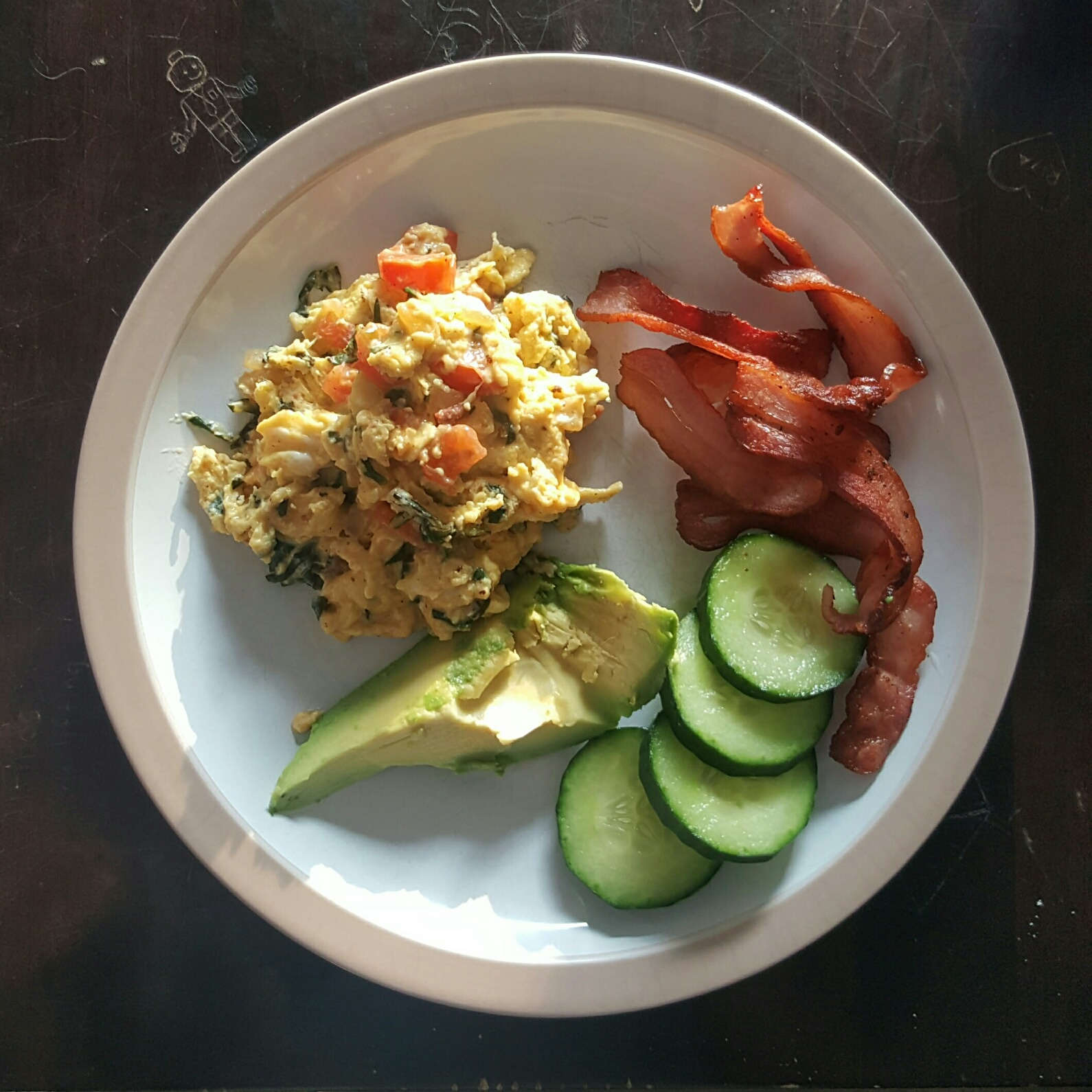 Spinach, tomato and onion scrambled eggs with bacon, cucumber and avo
