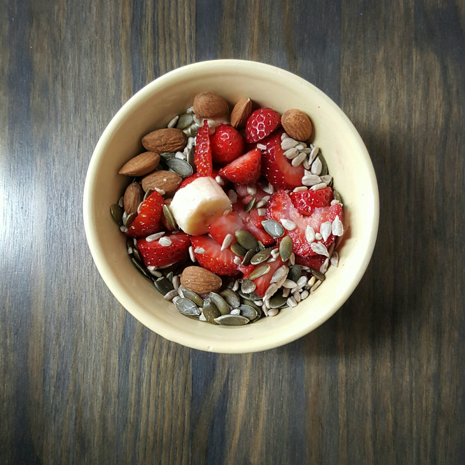 A banana, 4 strawberries and a handful of almonds, sunflower and pumpkin seeds